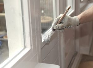 Painter brushing door trim